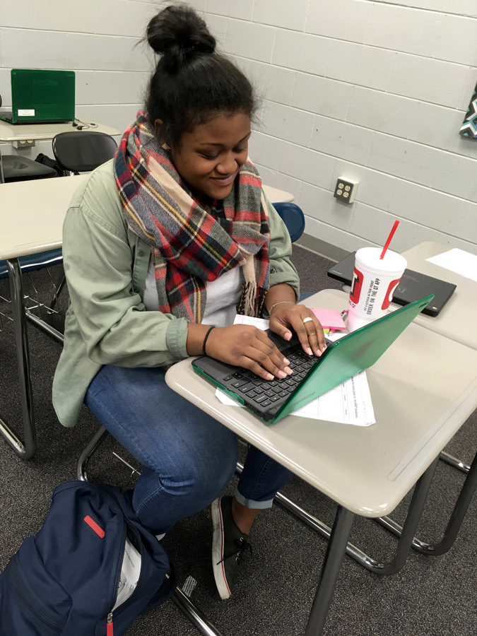 Junior+Fai+Thomas+works+on+her+Chrome+Book+during+her+6th+period+class.+She+wore+green+to+support+suicide+prevention+day+at+the+school.