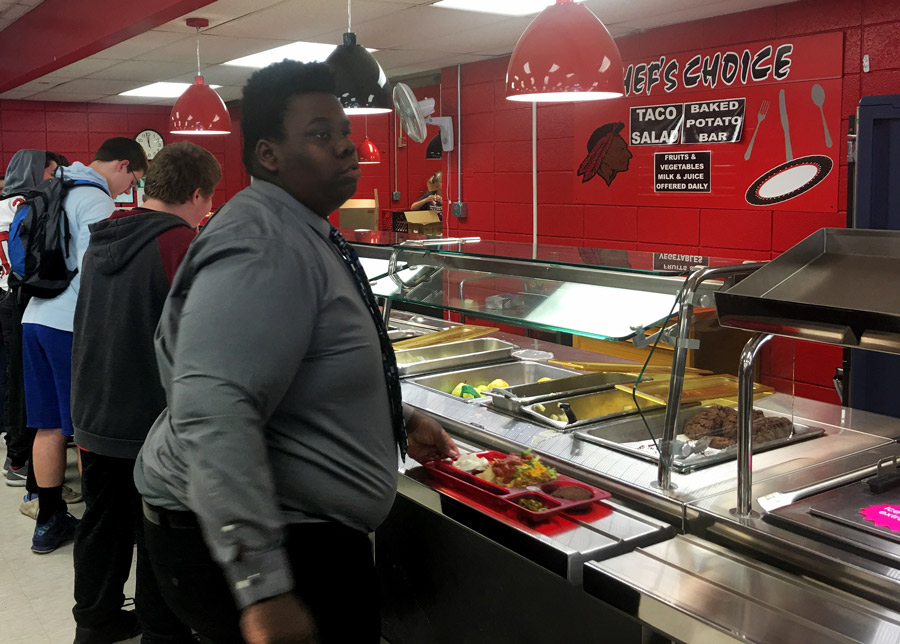 Junior Mylan Harris looks over the food items in the newly organized food station. The cafe started offering different options in the food lines at the start of November.