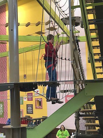 Junior Alex Zachgo traverses the team building obstacle at the 91st Annual FFA Convention in Indianapolis, IN. Eight students from the school attended the event Oct. 24-28.