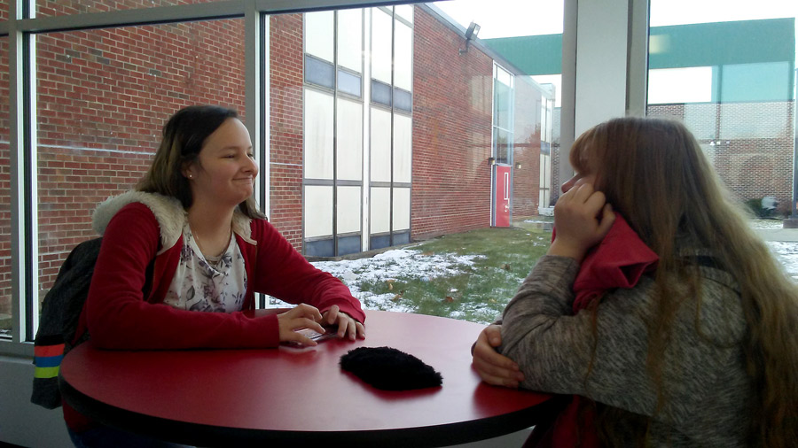 Sophomores Amber Waterman (L)-and Emaley Peevey enjoy some free time at the one of the tables in the enclosed breezeway. Students can stand at eight tables before school, during passing periods , during lunch and after school.