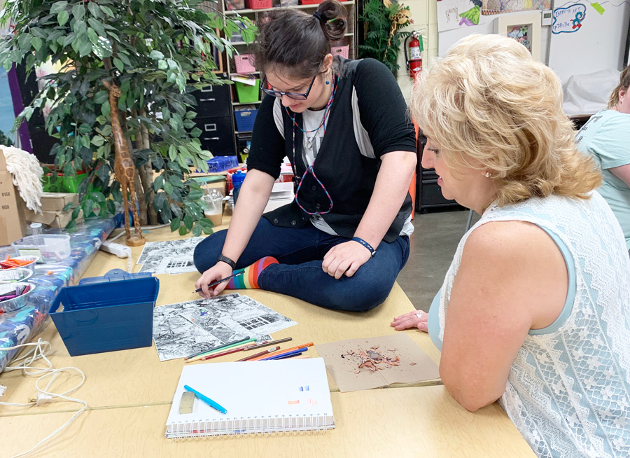 Looking over a piece of art, 2019 Teacher of the Year Ms. Kim Meneses works with junior Antoinette Hoke. Ms. Meneses is in her 11th year at the school.