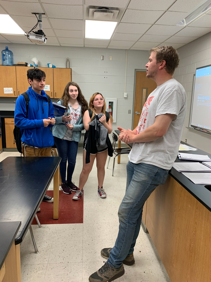 Finishing up a class, Mr. David Moore talks with freshmen Emme Jeffries, Kelsey Yocum and Linsey Hull as they leave. Mr. Moore and six other teachers/staff are leaving for other jobs at the end of the year.
