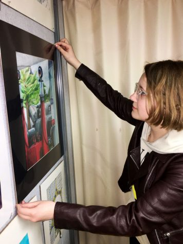 "Getting it just right, Junior Allison Gant adjusts a print of her award winning art work, ""Olde Town Road,"" that is on display at the district"