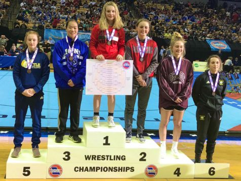 Freshman Haley Ward stands at the top of the podium with the 130 pound Championship bracket poster in her hands. Ward is the first Individual Girls Wrestling State Champion in FOHS history.