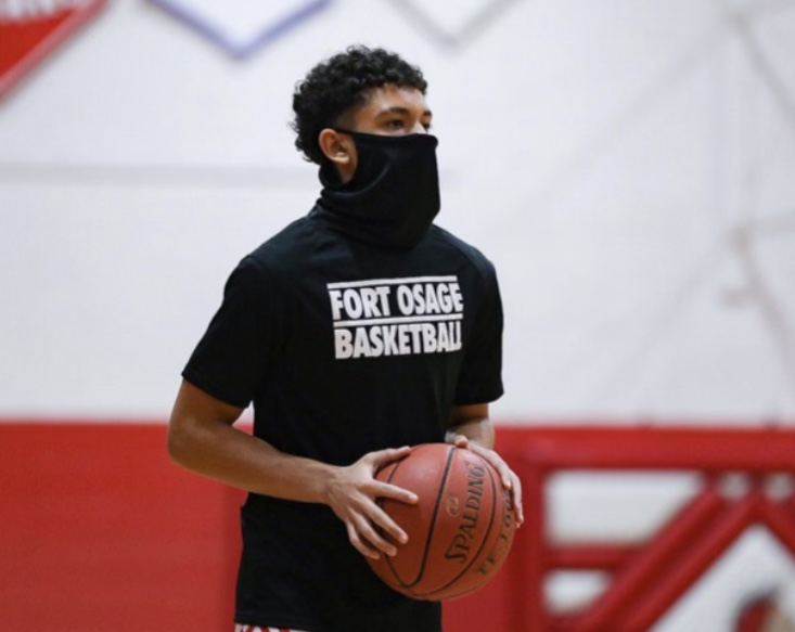 ADJUSTING TO THE TIMES. Running a pre-game drill, Senior Gabriel Franklin prepares to pass the ball. All sports have had to adjust to COVID-19 Restrictions which include social distancing, mask wearing and limited fan participation.