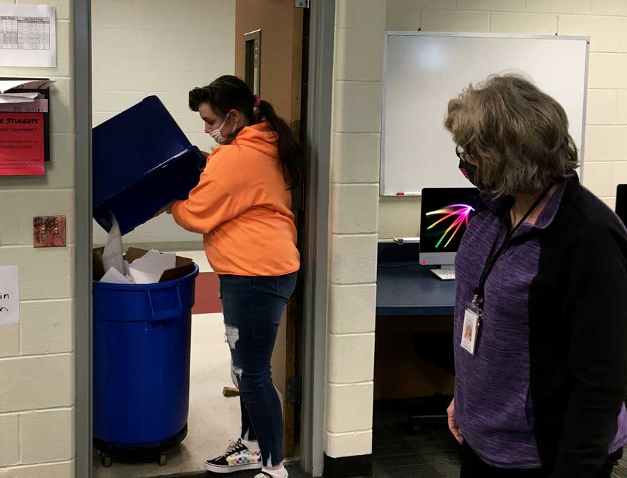RECYCLING RESUMES. Making the rounds, Junior Kelsey Farrar dumps a recycling tub into a collection can on a recent Friday under the supervision of Special Education Para Delana Jones. The Job Skills class resumed recycling efforts earlier this semester.