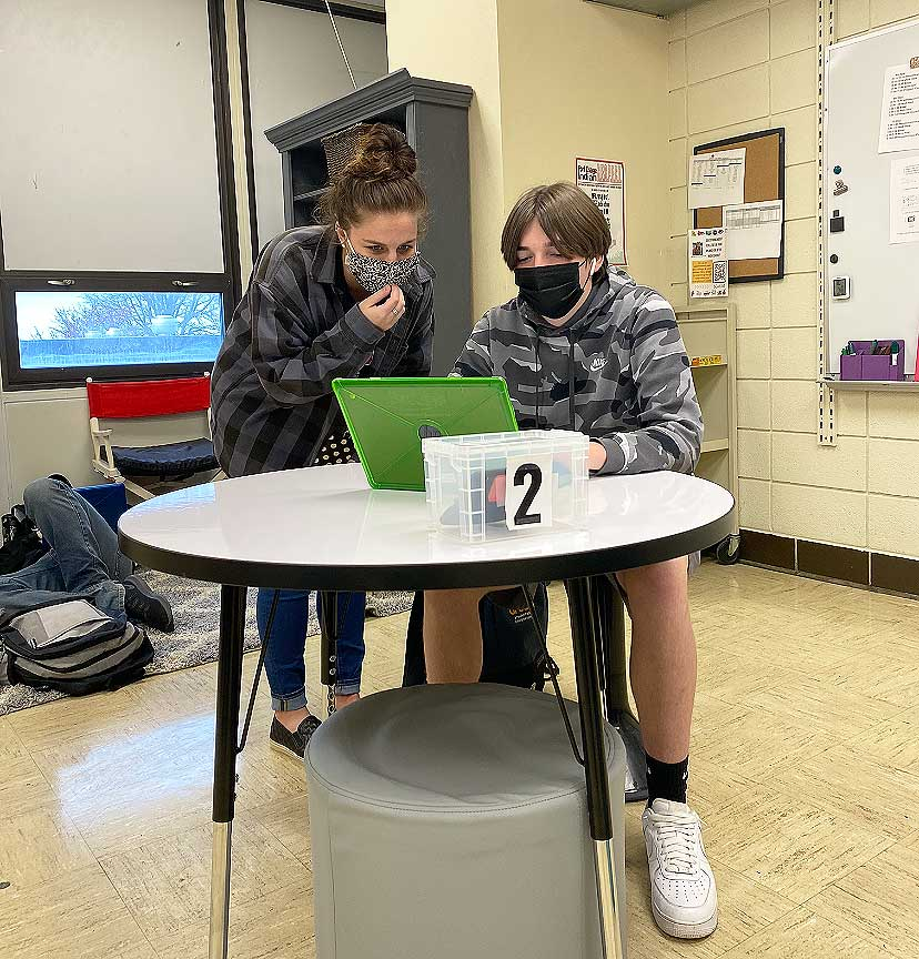STAYING ON TASK. Working on an assignment, Ms. Morgan Ewing helps Sophomore Drew Warren solve a problem. Ms. Ewing started working for the school in January of this year.