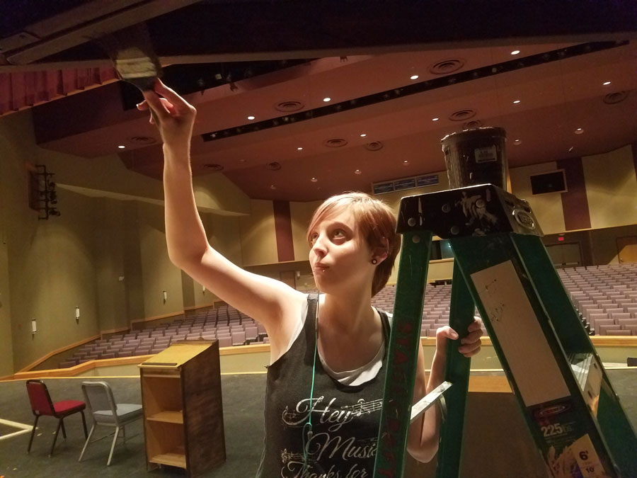 Junior Hope Robinson paints the set on the PAC stage for