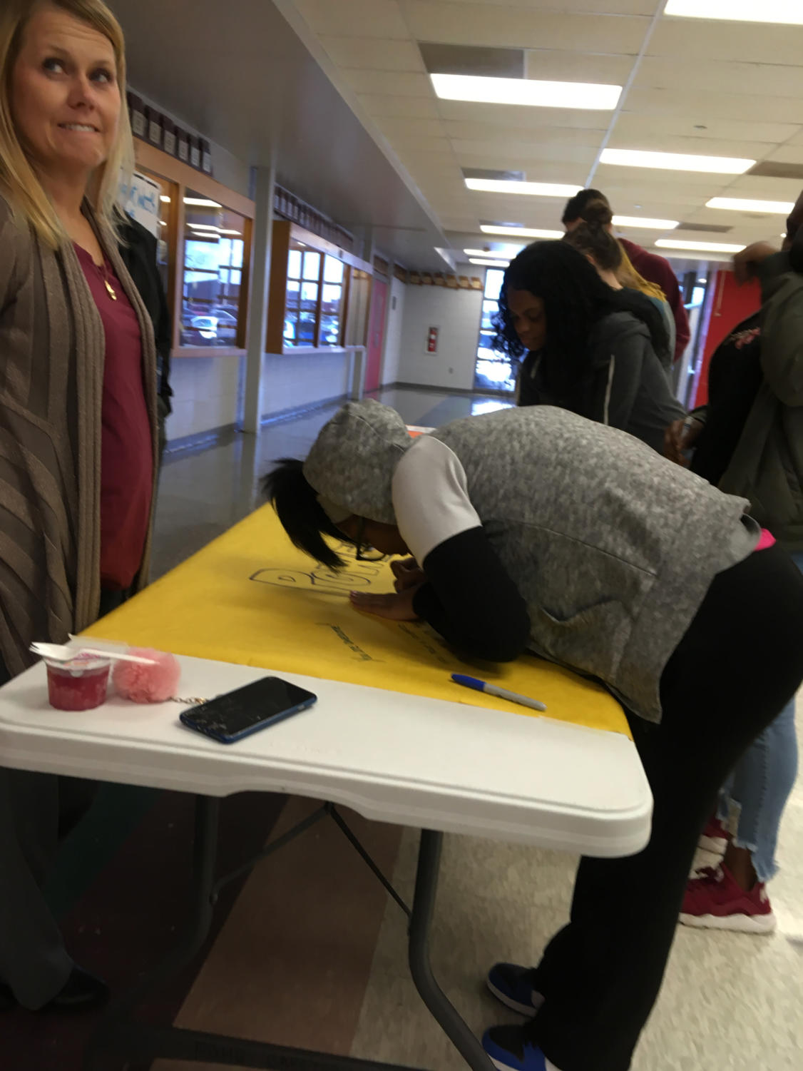 Junior Jemisha Nettles writes a message on poster paper during her lunch shift while Assistant Principal Tracie Gramko watches over the crowd. The poster paper will be hung around the building for students to view.