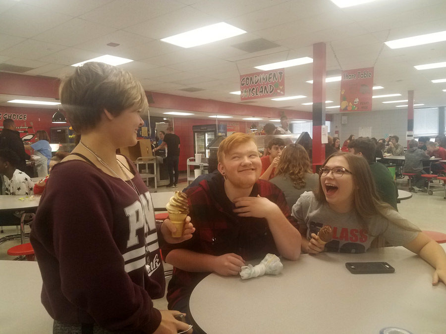 Sophomore Maycie Meaders tells a joke that made junior Mikeal Williamson and senior Emily Knox laugh and smile. One of the challenges for the day was to make five people smile with random acts of kindness.