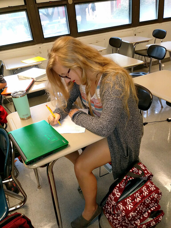 Senior Heylee Warren works on her homework during her spare time in chemistry class. She dressed as a hipster to represent her favorite genre during Homecoming Spirit Week.