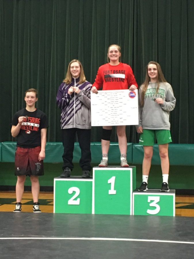 Junior+Tess+Kinne+stands+atop+the+podium+with+her+tournament+card+and+1st+Place+District+medal.+Kinne+was+the+first+in+school+history+to+win+an+individual+Girls+District+Wrestling+Championship.