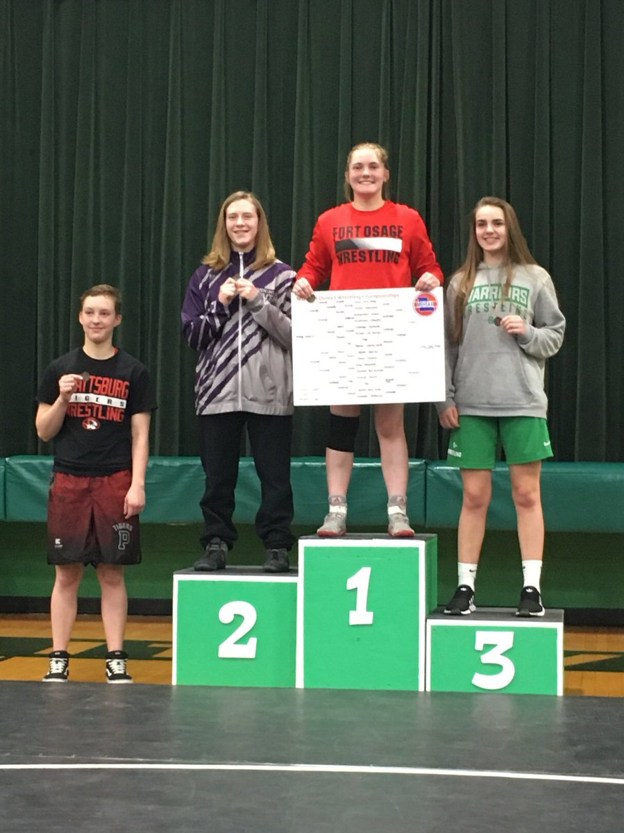 Junior Tess Kinne stands atop the podium with her tournament card and 1st Place District medal. Kinne was the first in school history to win an individual Girls District Wrestling Championship.