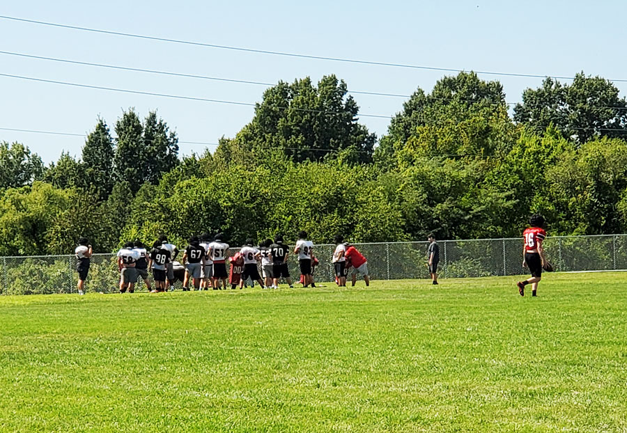 The varsity football team runs a play at a recent practice. The team begins the season on Aug. 30 at Raytown South.