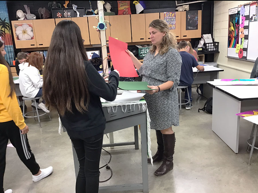 Ms. Renne Wright helps a student prepare for a project. She brings 13 years of teaching experience to the classroom.