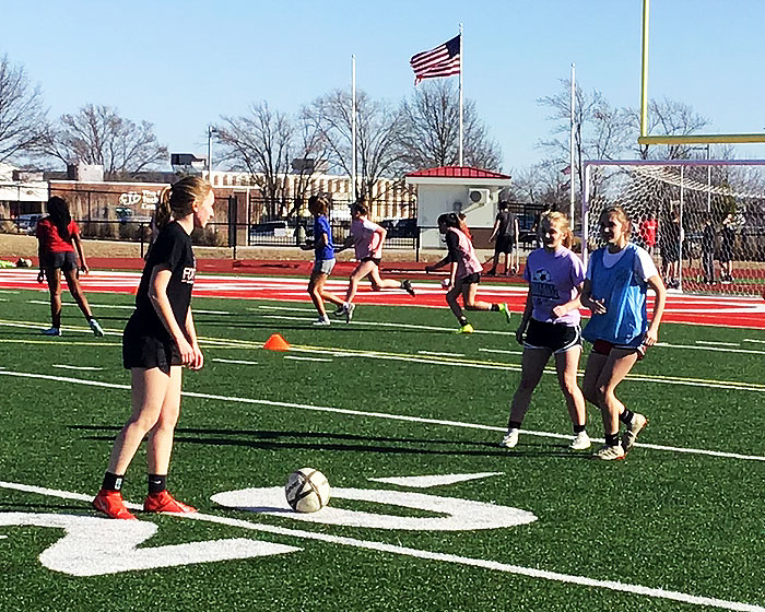 Senior Amanda Daniel prepares to kick the ball over Junior Ishbel Wilson and sophomore Elayna Lamb in a recent soccer practice. The team starts the season at home on March 20 against Ruskin.