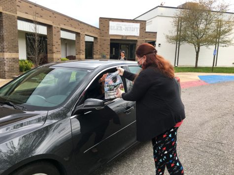 Meeting at a car, OTMS Teacher Ms. Allison Friedrich hands lunches to Ms. Susan Panther at Cler-Mont Elementary School. The district continues to deliver lunches for children 18 and under on Mondays and Thursdays at Cler-Mont Elementary, Blue Hills Elementary, Buckner Elementary, Elm Grove Elementary and Hawthorn.