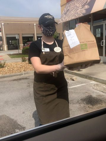 Working during the COVID-19 Shut Down, Junior Aubri Stewart hands a Panera Bread order to a curb-side customer. Food service companies like Panera were considered essential jobs which allowed teenage employees to still work during the Jackson County Stay at Home Order.