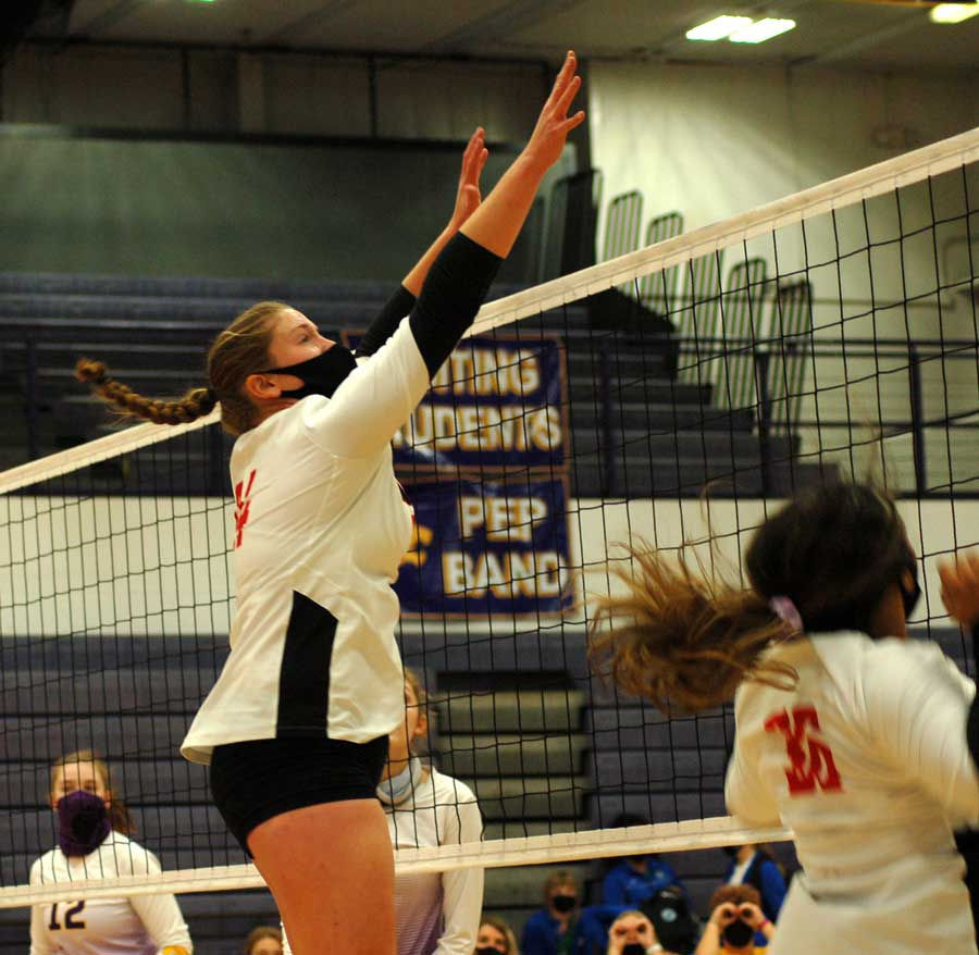 ABOVE THE NET. Stretching out her hands, Senior Kendra Seifker jumps to block a ball. Siefker finished her senior year with 183 kills, 10 unassisted blocks and 43 unassisted blocks.