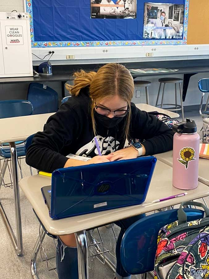 STAYING FOCUSED. Taking notes, Junior Olivia Siefker works hard at getting assignments done as the last day of the semester approaches. The District moved the last day from Dec. 22 to Dec. 18, 2020.