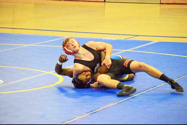 TIGHTEN THE GRIP. Going for the pin, Senior Jeremiah Phillips works to secure his opponents back to the mat. Phillips finished the Class 3 District 8 tournament as the 160 lb. Champion.