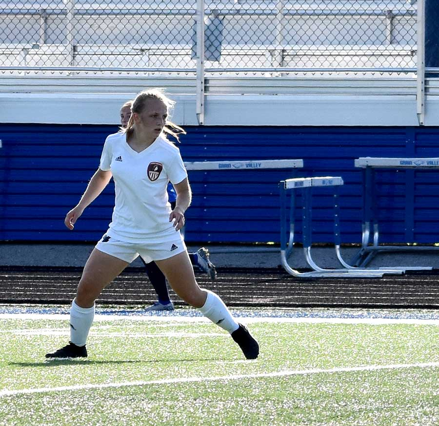 GUARDING THE MIDDLE.  Surveying the field, Senior Midfielder Isbel Wilson sets up to intercept the ball in a match against Grain Valley. Wilson scored two goals this season for the Indians.