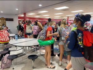 WAITING. Keeping busy, students check their phones and visit while waiting in the unusually long lunch lines. The school year started with increased congestion due in part to a change from six lunch shifts to four lunch shifts.