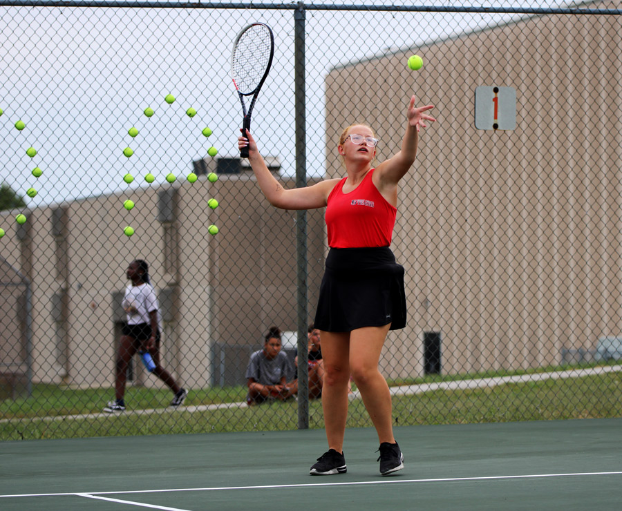 SERVE. Tossing the ball in the air, senior Alanis Cameron served during her singles match against Grandview. The team beat the Bulldogs 9-0 on senior night.